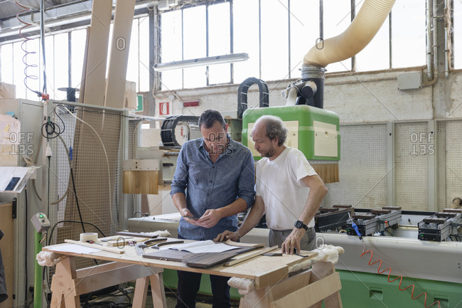 Project manager and coworker working while standing against sawing machine at factory