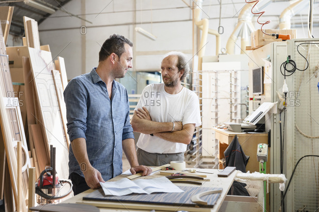 Smiling project manager talking with coworker while standing in factory