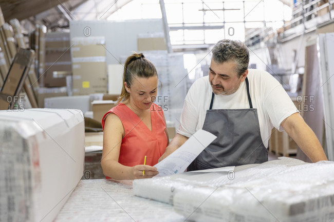 Secretary checking shipment paper while standing by coworker at factory