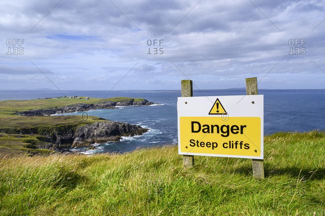 UK- Scotland- Warning sign in front of steep cliffs ofTiumpanHead