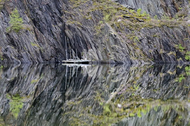 Slate cliffs reflecting in clear shiny lake in Scottish Highlands