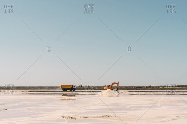 Spain- Province of Huelva- Huelva- Clear sky over truck and earth mover working in salt flat