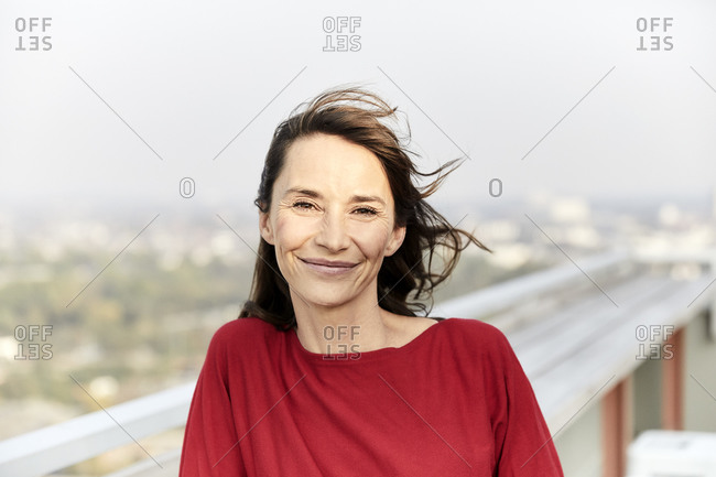 Smiling woman with hair blowing standing on building terrace