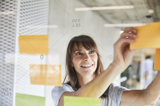 Woman smiling while sticking sticky notes on glass material