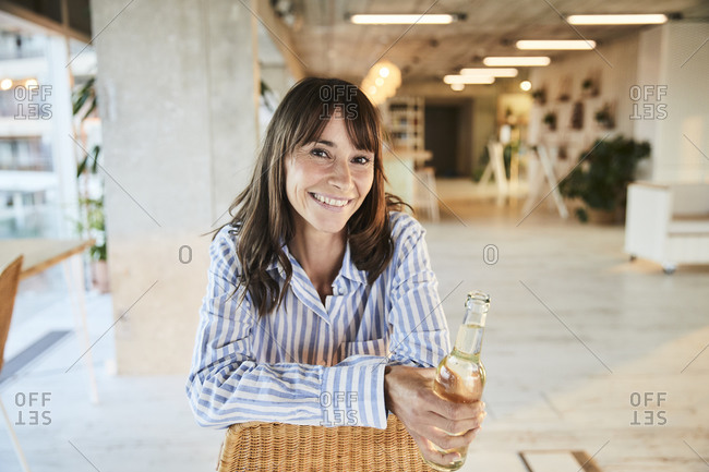 Smiling mature woman holding beer bottle while sitting at home