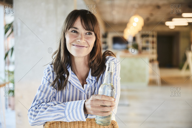 Smiling mature woman looking away while holding beer bottle sitting at home