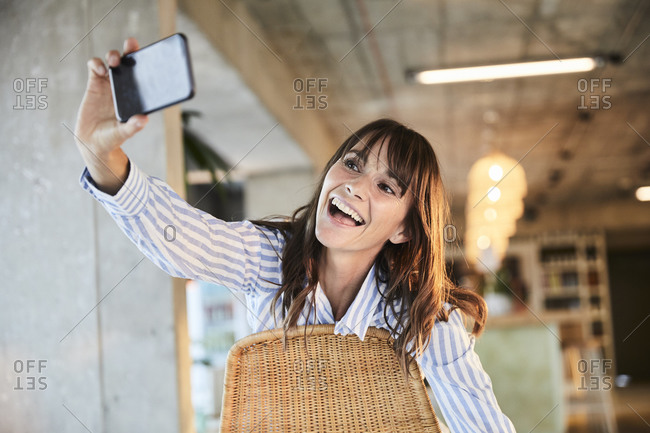 Happy mature woman with mouth open taking selfie on smart phone while sitting at home