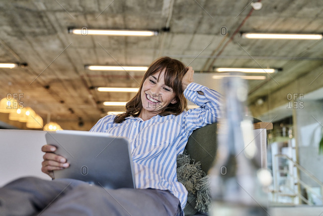 Smiling woman with hand in hands using digital tablet while sitting on sofa at home