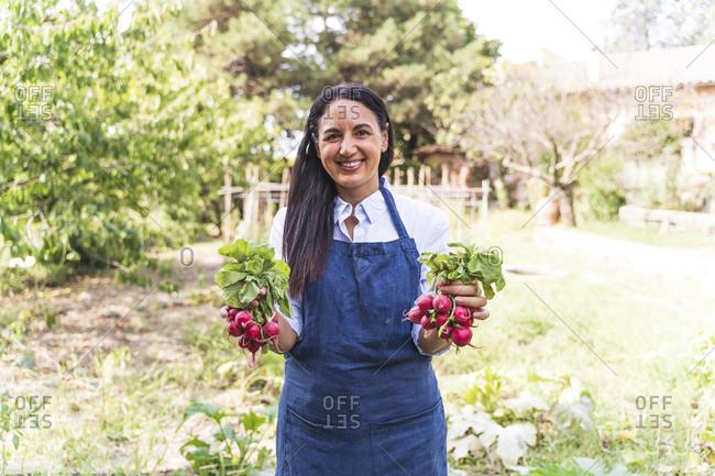 Happy woman holding fresh radishes at vegetable garden