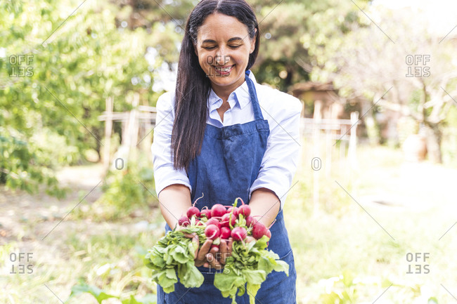 Happy woman showing freshly harvested organic radishes from garden