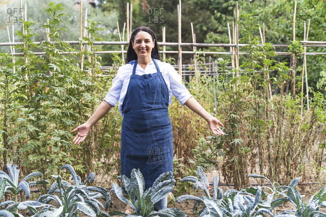 Smiling mature woman with arms outstretched standing by fresh organic kale plants at vegetable garden