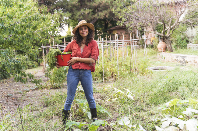 Smiling beautiful woman holding harvested vegetable in bucket at garden