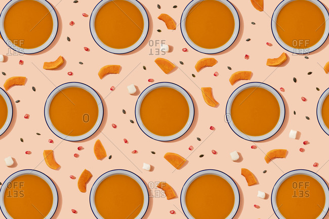 Pattern of bowls of pumpkin soup surrounded by pumpkin seeds- pomegranate seeds and pieces of cheese and pumpkin