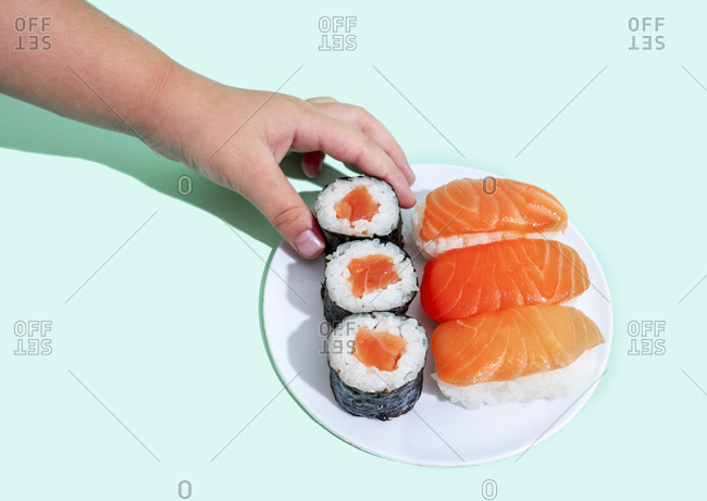 Hand of little girl picking up piece of maki sushi