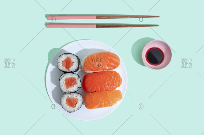 Studio shot of chopsticks- bowl of soy sauce and plate of maki sushi and nigiri