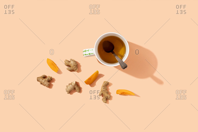 Studio shot of mug of herbal tea- ginger roots and peach slices