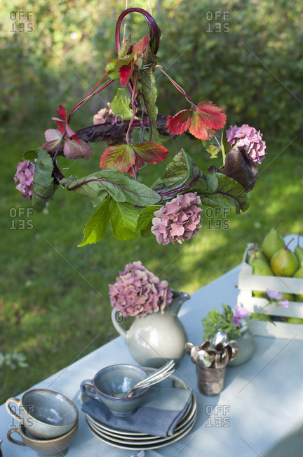 DIY Lamp shade made of beetroot leaves and blooming hydrangeas hanging over coffee table set in garden