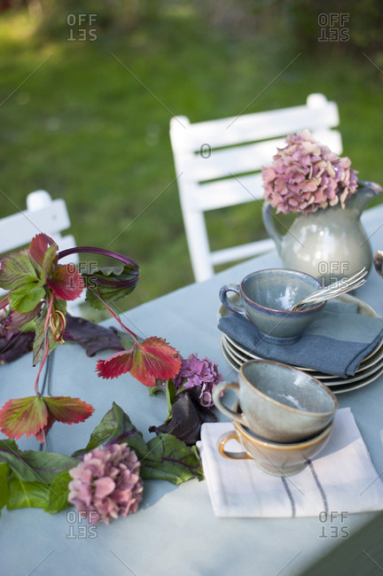 Crockery and DIY lamp shade made of leaves and hydrangea flowers lying on coffee table set in garden