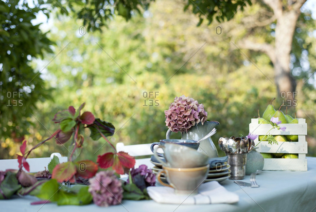 Crockery- DIY lamp shade and jug with blooming hydrangeas lying on coffee table set in garden