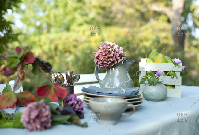 Crockery-DIYlamp shade and jug with blooming hydrangeas lying on coffee table set in garden