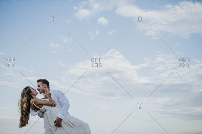 Young couple looking at each other while dancing against clear sky