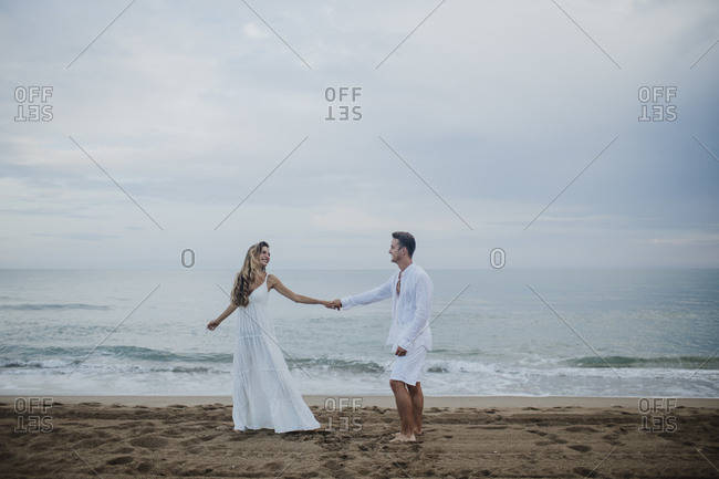 Couple holding hands while dancing against sea at beach