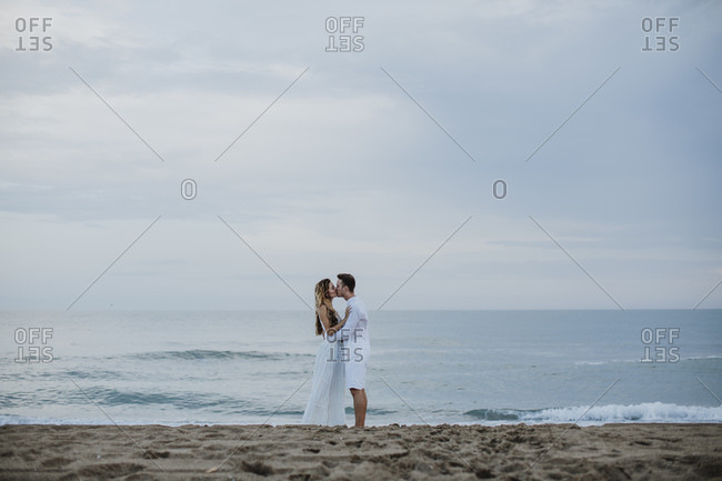 Couple kissing each other while standing against sea at beach