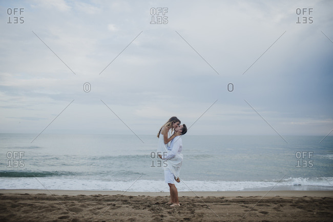 Romantic boyfriend carrying girlfriend while standing on beach