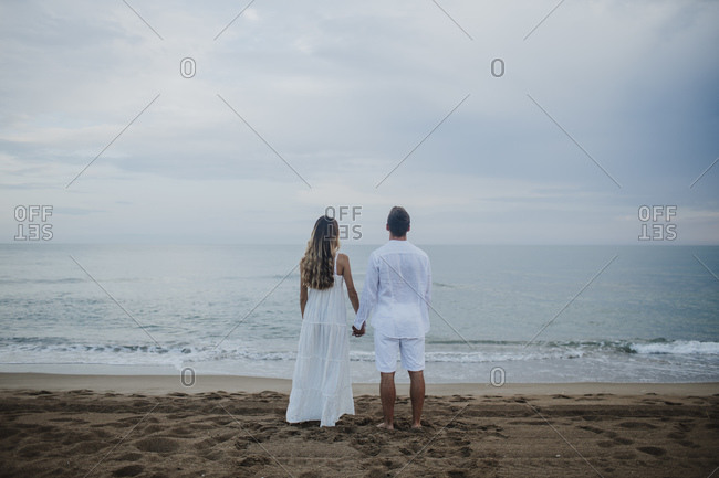 Couple holding hands while admiring sea view standing at beach