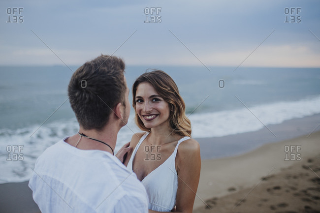 Smiling woman standing with man on beach