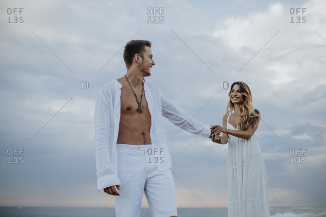 Smiling woman holding hand of man while standing against sky