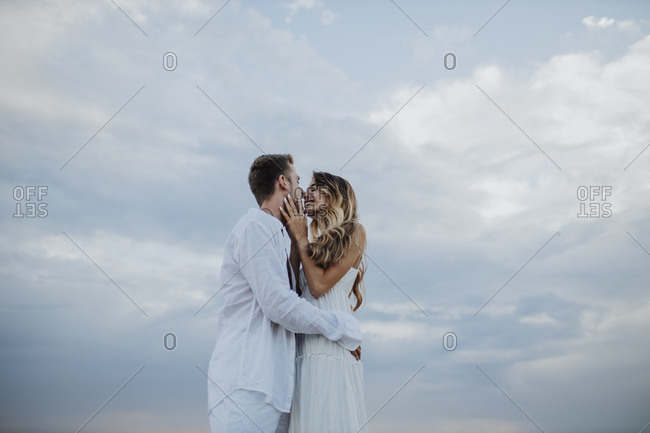 Young couple rubbing nose while standing against sky