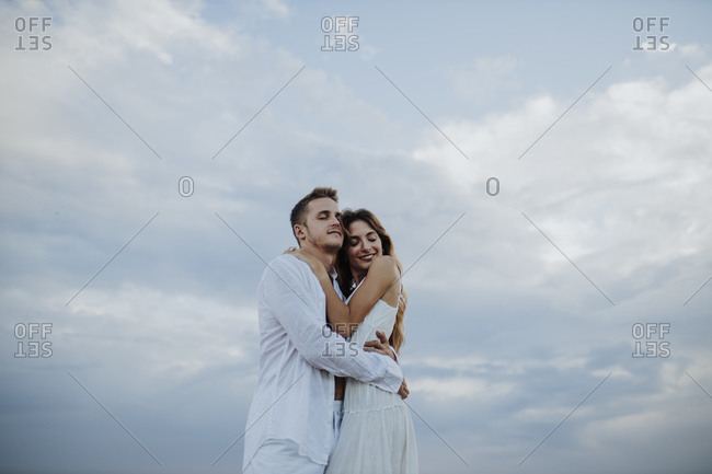 Couple embracing each other while standing against sky