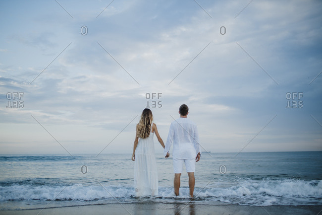 Couple holding hand while admiring view standing at water's edge on beach