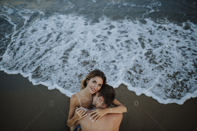 Couple embracing each other while sitting at water's edge on beach