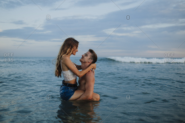 Boyfriend carrying girlfriend while standing in water at beach