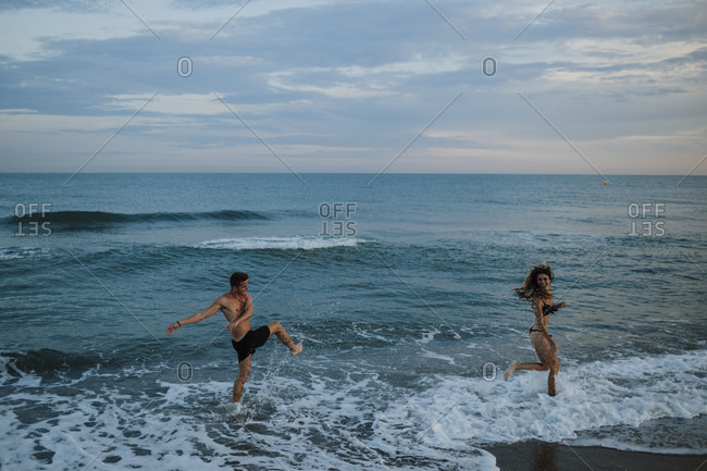 Young couple enjoying while playing at beach