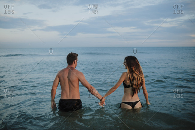 Couple wearing swimwear holding hand while standing in water at beach