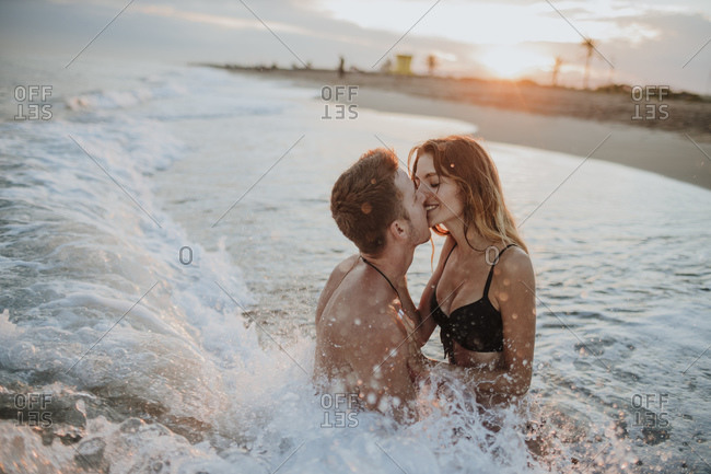 Couple doing romance while sitting in water at beach