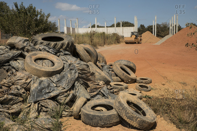 Pile of different tires on dump with bulldozer in background