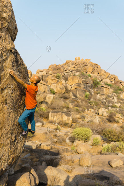 Male rock climber ascending rock wall with hill in background