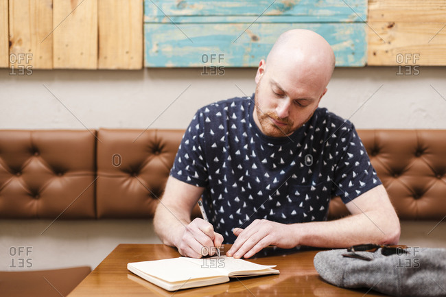 Mid adult man writing in notebook while sitting in cafe