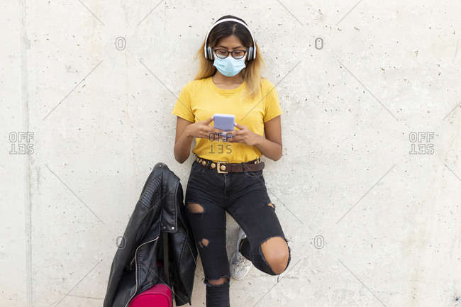 Young woman wearing protective mask while using smart phone by luggage against white wall at bus stop