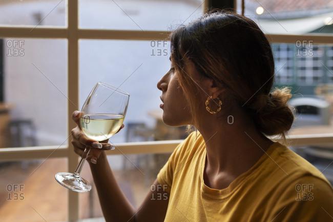Beautiful Latin woman drinking white wine at bar