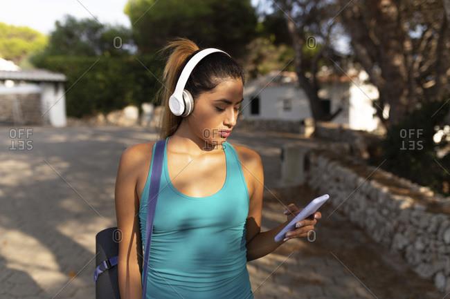 Young Hispanic woman using smart phone while listening music