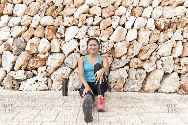 Smiling beautiful young woman listening music through headphones while sitting against stone wall after exercising