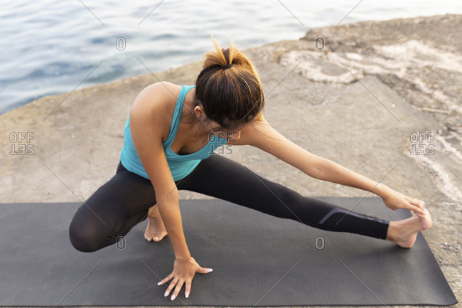 Young woman stretching on exercise mat at promenade against sea