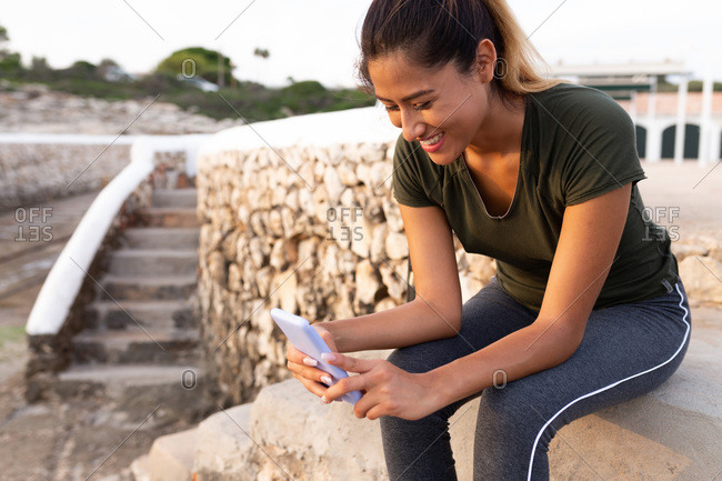Smiling beautiful Hispanic woman using smart phone while sitting outdoors