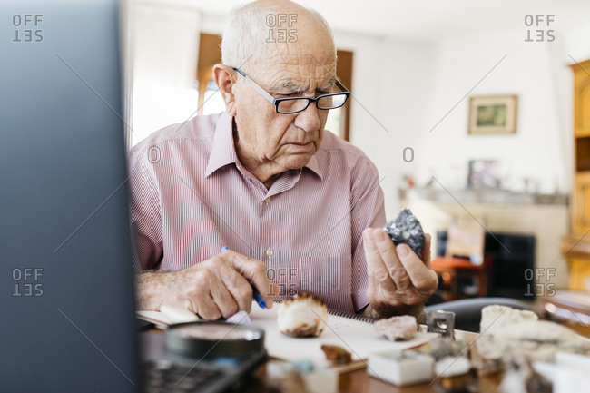 Elderly man analyzing minerals and fossils while sitting at table