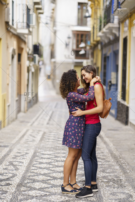 Couple doing romance while standing on footpath in city